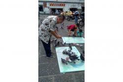 El artista Luis Fernando Arias hizo sus pinturas en el parque principal, usando a las palomas que se aglomeran en el sector.