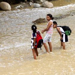 Protegiendo sus pertenencias del agua, los niños del barrio El Porvenir deben cruzar este río a diario para asistir a clases hasta el barrio Galán en Bucaramanga.