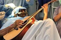 Un músico indio toca la guitarra mientras le operan el cerebro