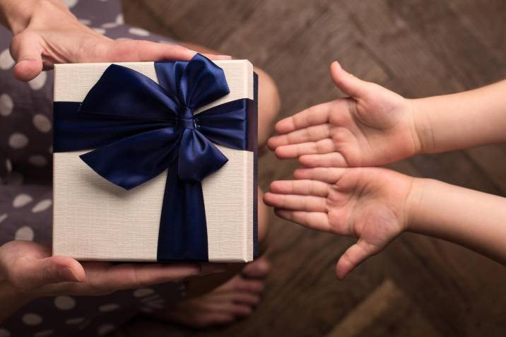 Top view of hands of mother giving one large gift box with blue ribbon to her kid with open hand