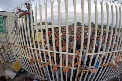 Inmigrantes hondureños pasan a la fuerza barrera policial y entran a México